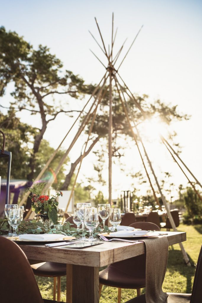A teepee set up in a backyard with a beautiful tablescape.